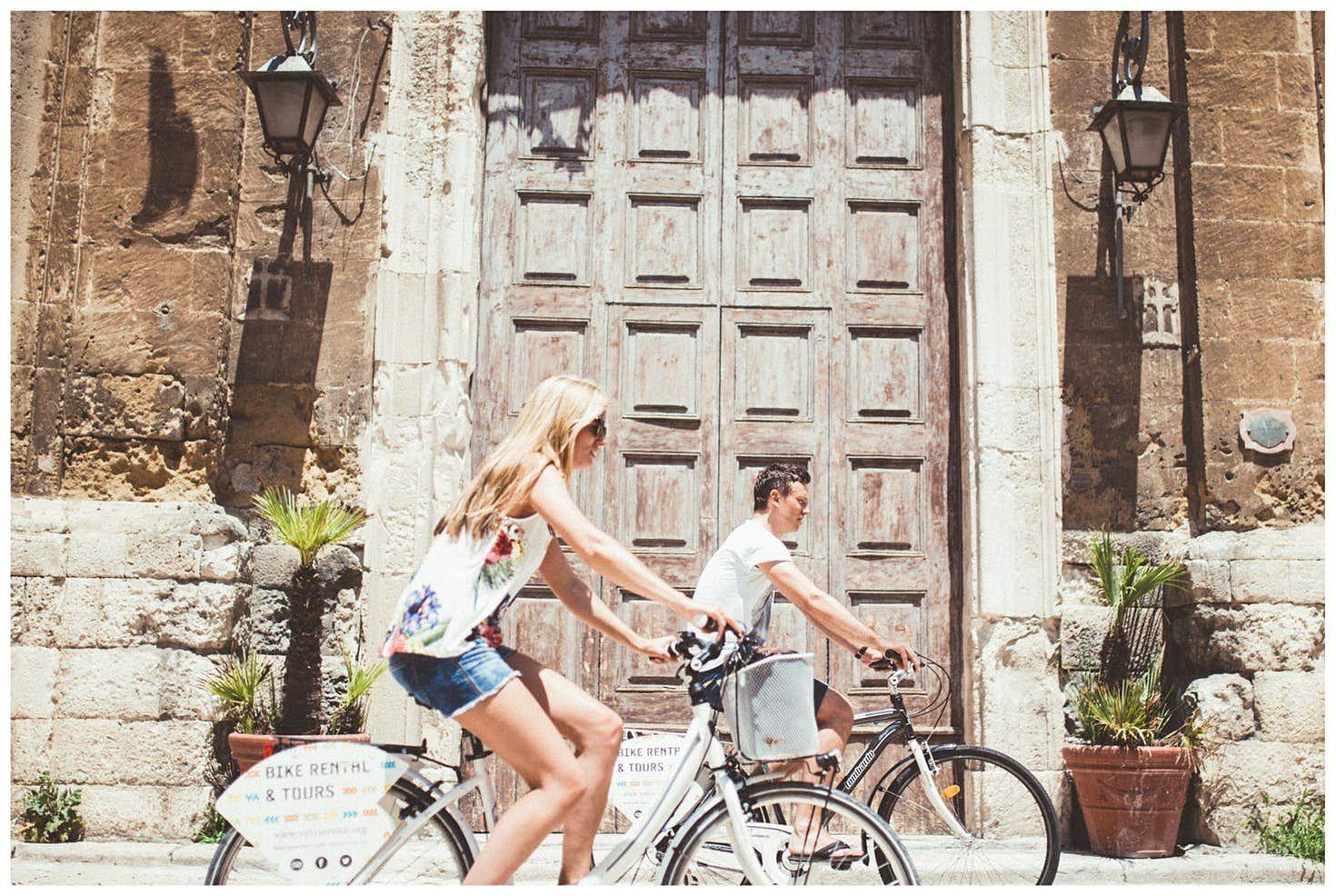 Due turisti esplorano in bici le strade della Città Vecchia di Bari